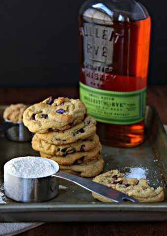 Whiskey Brown Butter Chocolate Chip Cookies on baking sheet with measuring cup of flour and bottle of rye whiskey to side