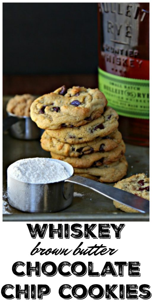 Whiskey Brown Butter Chocolate Chip Cookies. on a baking sheet with measuring cup of flour and bottle of rye behind