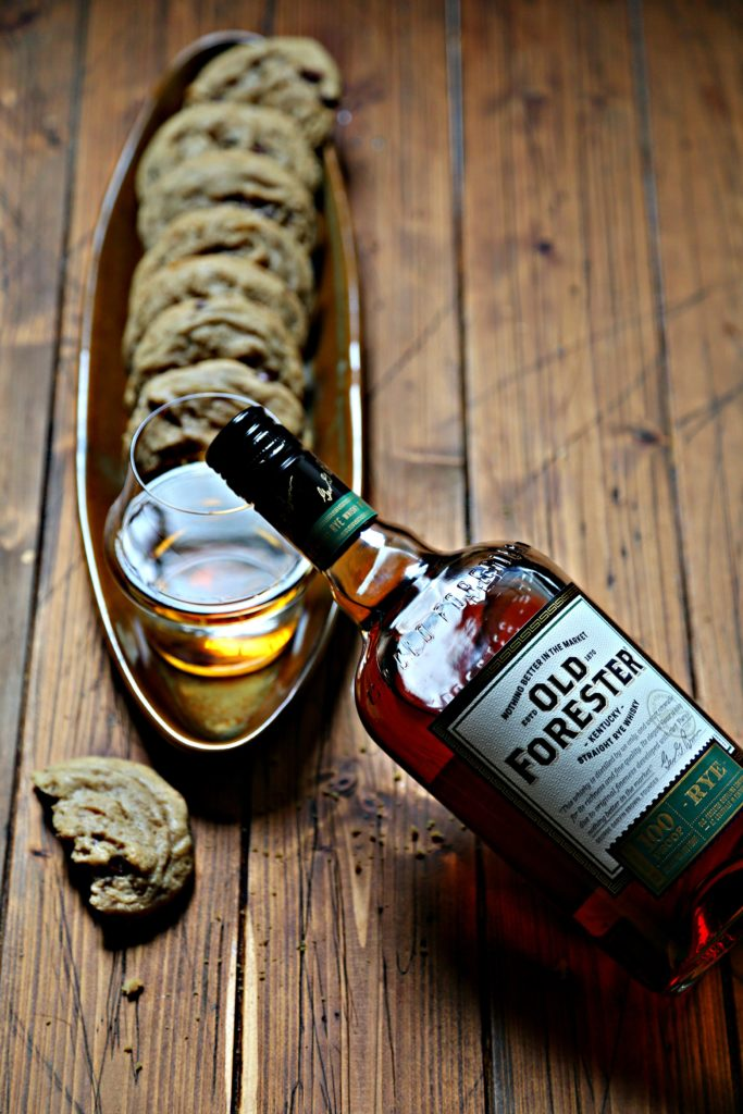 Whiskey Brown Butter Chocolate Chip Cookies Bottle of whiskey and broken cookie in front.