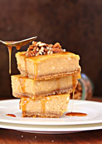 Pumpkin Cheesecake Bars with Whiskey Caramel Sauce stacked on plate