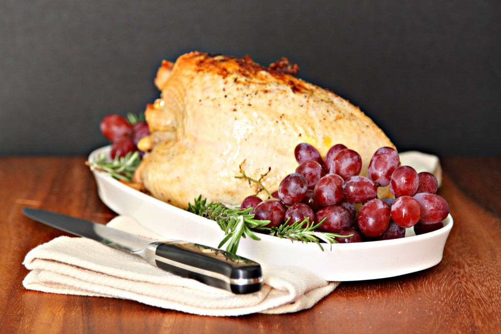 Roasted Turkey Breast on white tray with grapes and fresh rosemary.  Knife and napkin in front of tray.