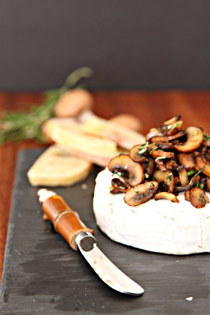 Savory Baked Brie with Crispy Mushrooms on a slate board. Cheese knife to side. Mushrooms and rosemary behind.