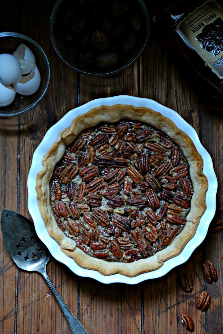 Bourbon Ginger Pecan Pie with egg shells, pecans, pie server and bourbon to side
