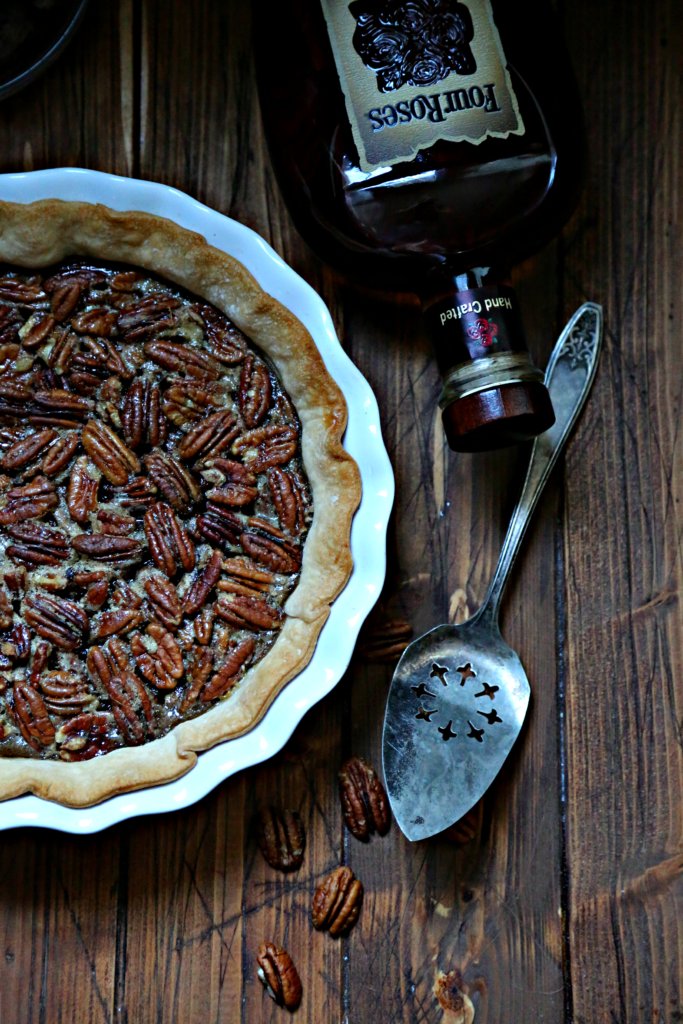 Bourbon Ginger Pecan Pie with bourbon and server to side
