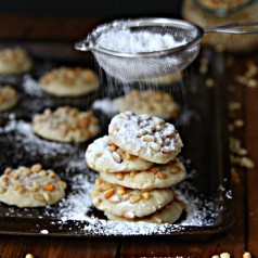 Pignoli Cookieson baking sheet with powdered sugar being shaken on top