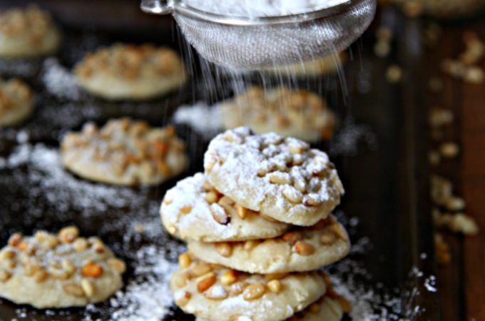 Pignoli Cookieson baking sheet with powdered sugar being shaken on top