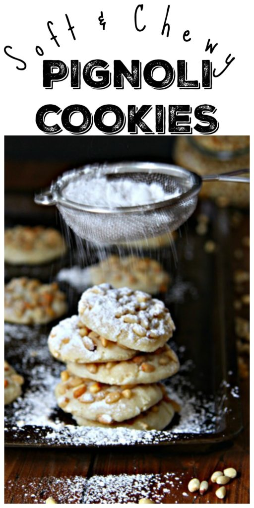Pignoli Cookies on baking sheet with sifter sifting powdered sugar on top. Text overlay reads soft & chewy pignoli cookies.