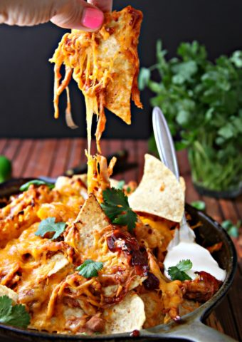 BBQ Chicken Nachos in skillet with fingers pulling nacho up.