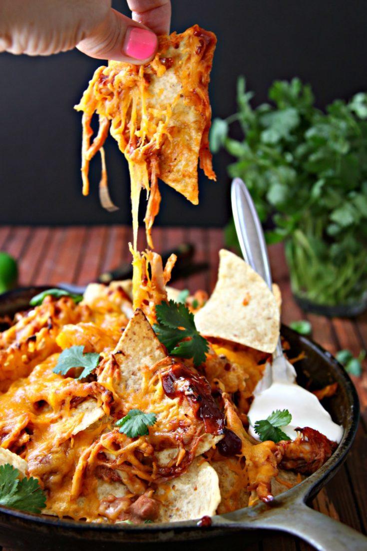 BBQ Chicken Nachos in skillet with fingers pulling nacho up.