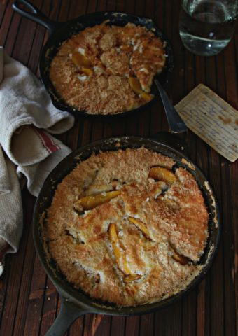 Peach Cobblers in black skillet with recipe card to side.
