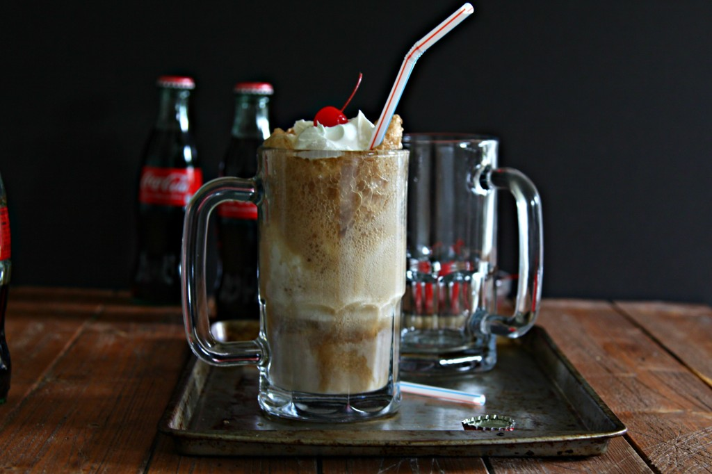Bourbon Cherry Coke Float in glass mug with straw on baking sheet. 2 bottles of Coca-cola in background.