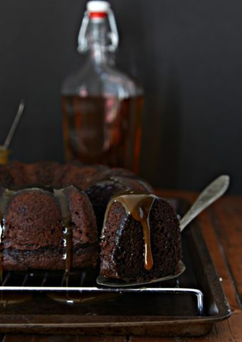 chocolate bundt cake on cooling rack. Slice of cake being pulled out. Bottle of bourbon behind.