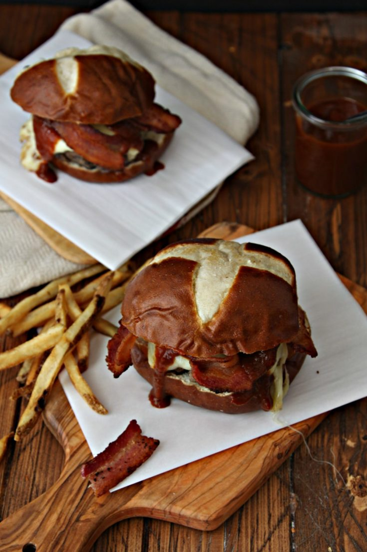 BBQ Bourbon Bacon Burgers on cutting board with fries and extra sauce to side