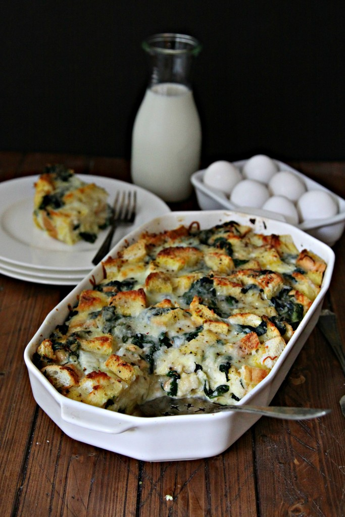Cheesy Spinach Strata in white baking dish. Glass jar of milk, half dozen eggs, and plate with slice of strata behind.
