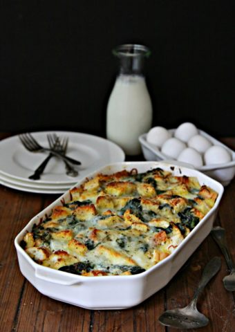 Cheesy Spinach Strata in white baking dish. Half dozen eggs, glass jar of milk, plates and forks behind.