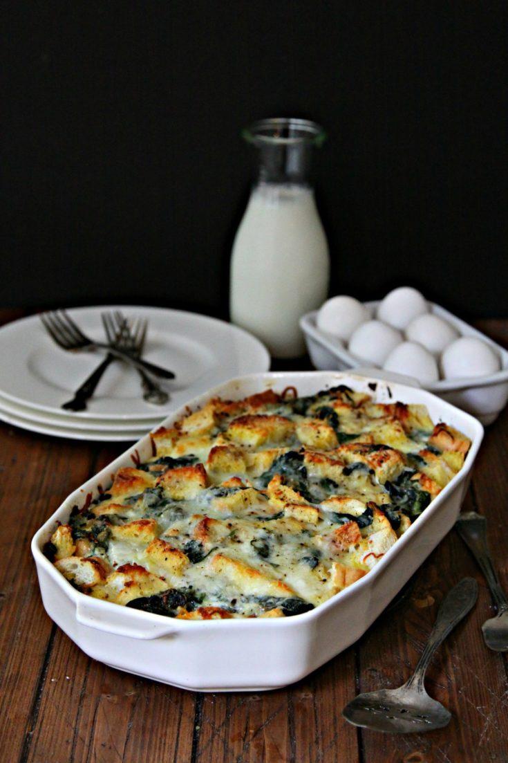 Cheesy Spinach Strata in white baking dish. Half dozen eggs, glass jar of milk, plates and forks behind.