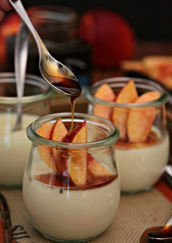 Vanilla Bean Panna Cotta with Nectarines and Honey in jars with spoon drizzled honey on top