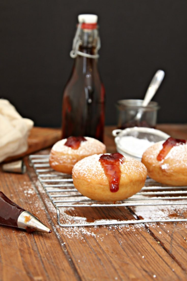 Bourbon Cherry Filled Doughnuts on a baking rack with bottle of extract to side and piping bag of cherry filling