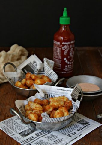 Fried Cheese Curds in silver bowls with sriracha bottle behind and dipping sauce