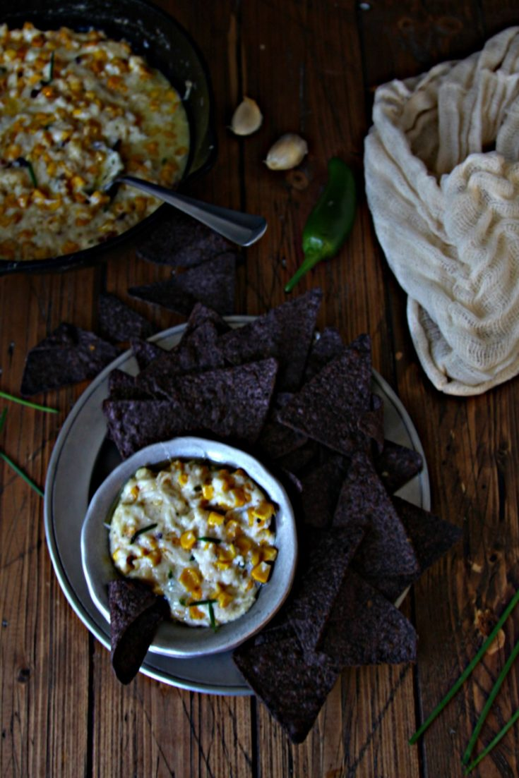 Spicy Corn Dip in silve bowl surrounded by blue corn chips on plate