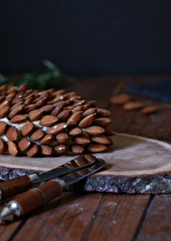 pine cone shaped holiday cheeseball on wood trivet with almonds and crackers to side