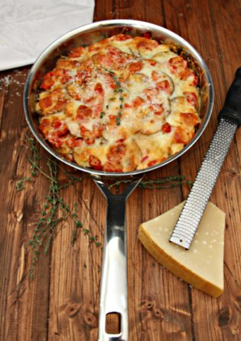 Potato Tomato Leek Gratin in skillet. Microplane with wedge of cheese to side, along with fresh thyme sprigs.