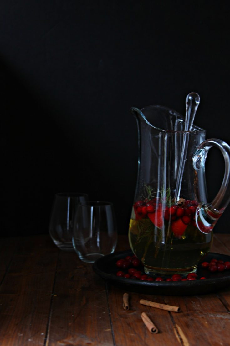 Christmas Sangria in glass pitcher with glasses behind