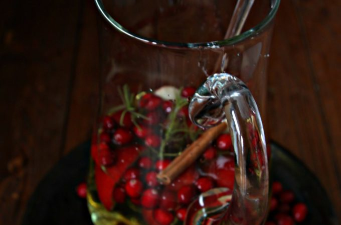 Christmas Sangria in white pitcher. Cranberries scattered around.