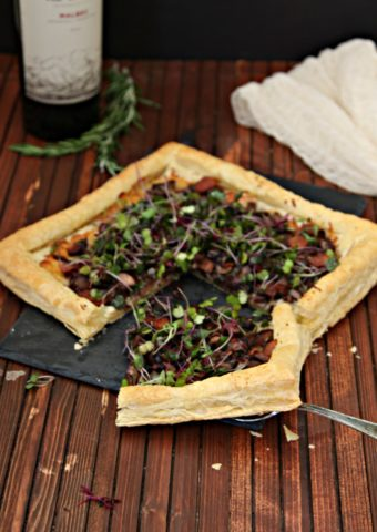 mushroom and bacon puff pastry tart served on a cheese slate pictured with wine bottle and rosemary sprig
