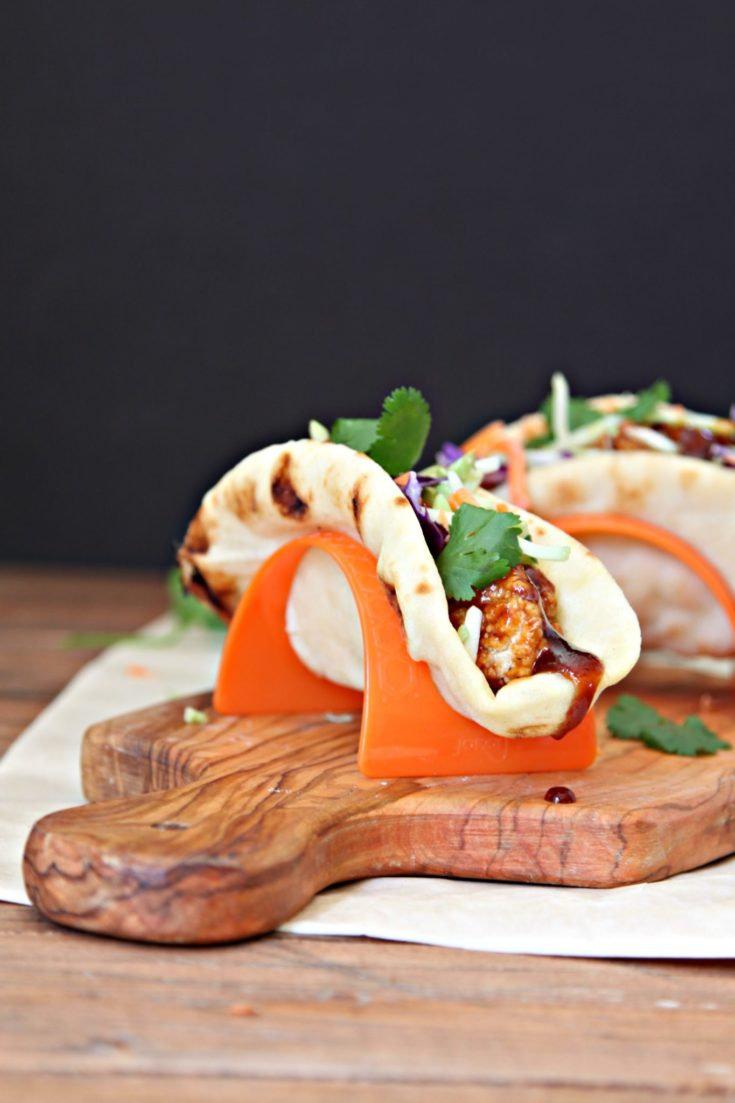 BBQ Chicken Naan Tacos in taco stands on cutting board.