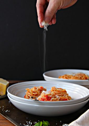 Spaghetti with Butter Roasted Tomato Sauce in white bowl. Hand sprinkling parmesan cheese onto bowl.