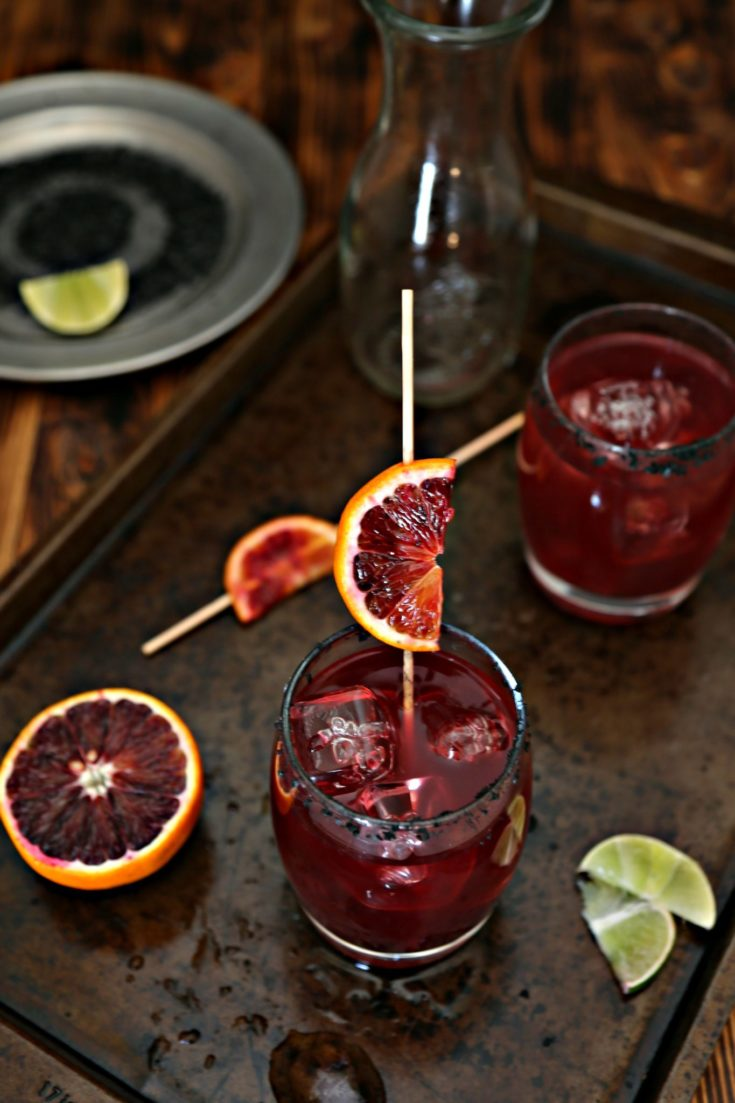 Blood Orange Margaritas on baking sheet. slice of blood oranges to side. Lime wedge to side.