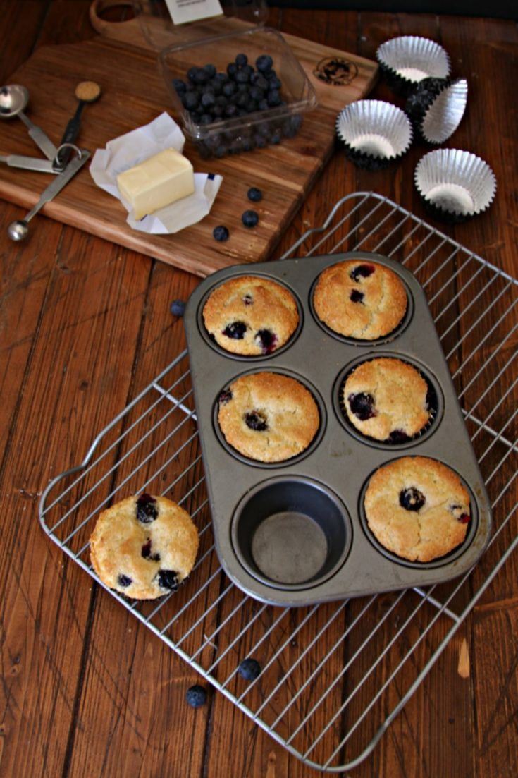 Blueberry Muffins in tin on cooling rack. Muffin ingredients behind.