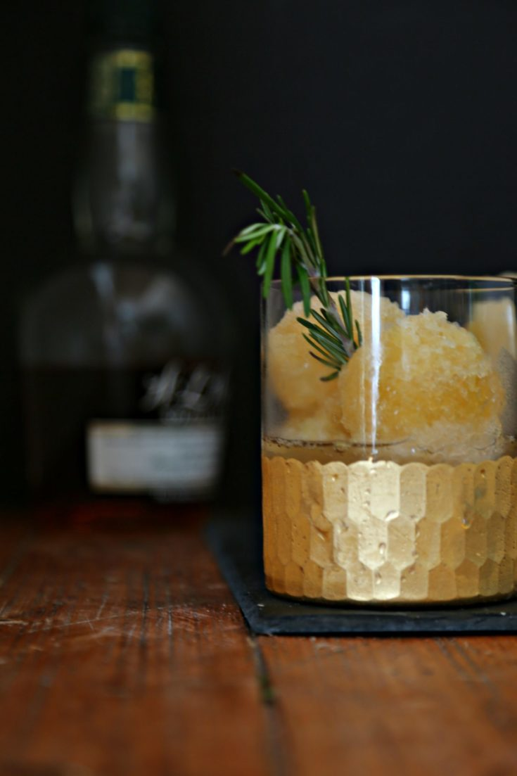 Bourbon Slush in glass with gold rim. Bottle of whiskey behind.