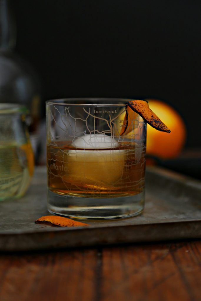 Old Fashioned cocktail in rocs glass with ice sphere on baking sheet