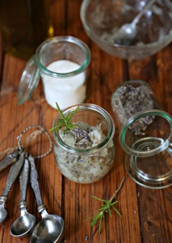 Rosemary Lavender Sugar Scrub in sall glass jars. Measurings spoons, jar of sugar and rosemary sprigs to side.