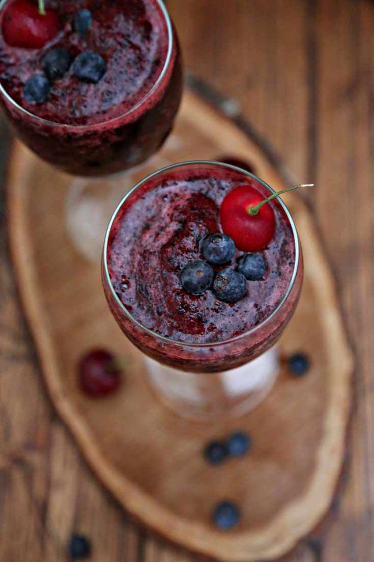 two glasses of Frozen Sangria on wood trivet. Blueberries scattered around.
