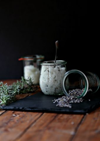 DIY Lavender Orange Sugar Scrub in small glass jars. Fresh rosemary sprigs to side, plus jar of coconut oil with spoon.