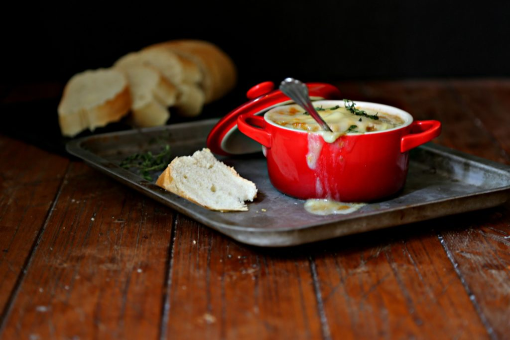 French Onion Soup in red ramekin on baking sheet with spoon in soup. Slices of bread in background.