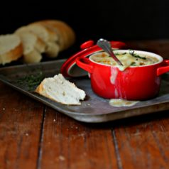 French Onion Soup in a red ramekin on a baking sheet