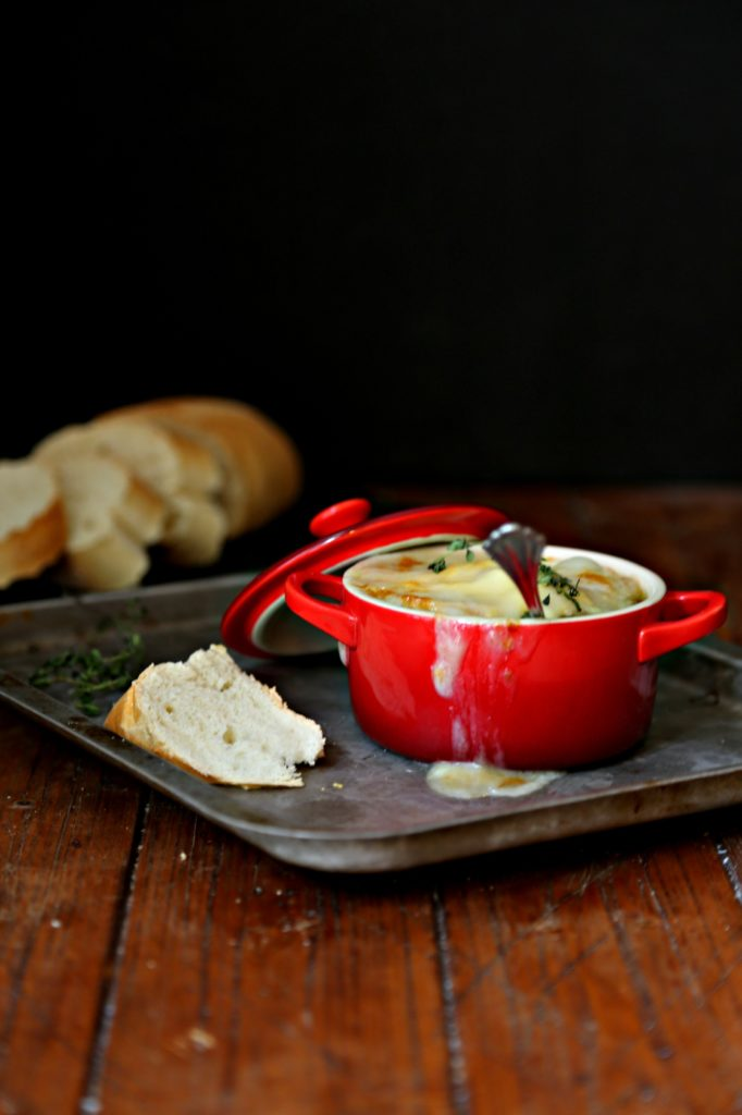 French Onion Soup in red ramekin with spoon on baking sheet. Slices of bread in background.