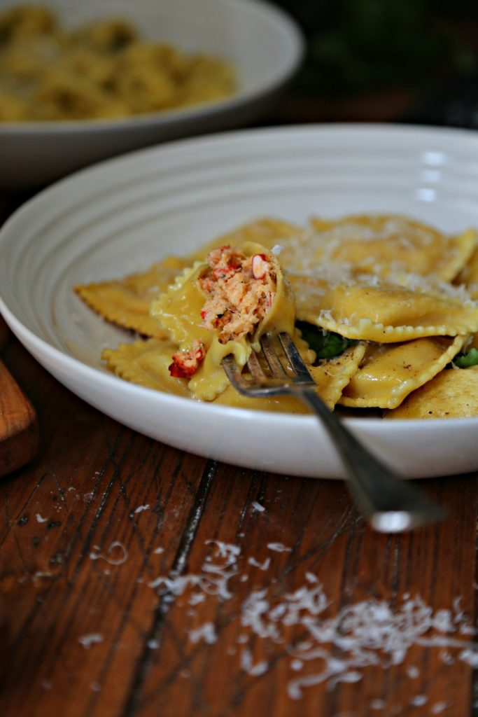 White bowls of lobster ravioli. Fork in front bowl with ravioli filling visible
