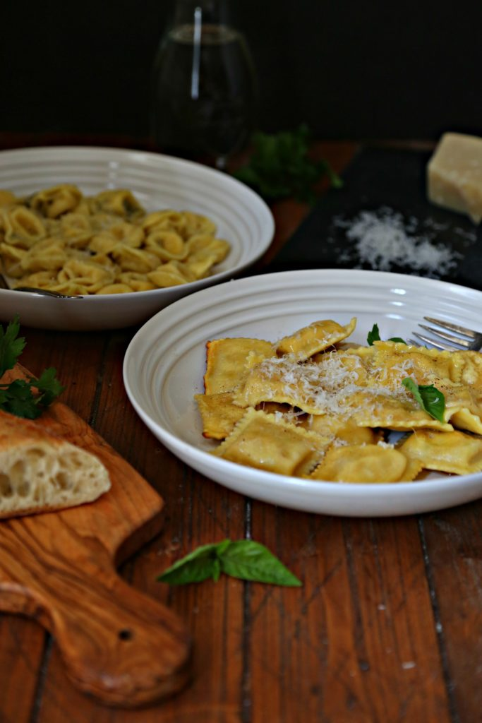 2 white bowls of Lobster Ravioli in Browned Butter Sauce. Cutting board with bread in front. Slate with grated cheese in background.