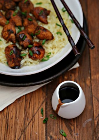 White bowl of bourbon chicken over sticky rice. Chopsticks and small jar of glaze to sides.