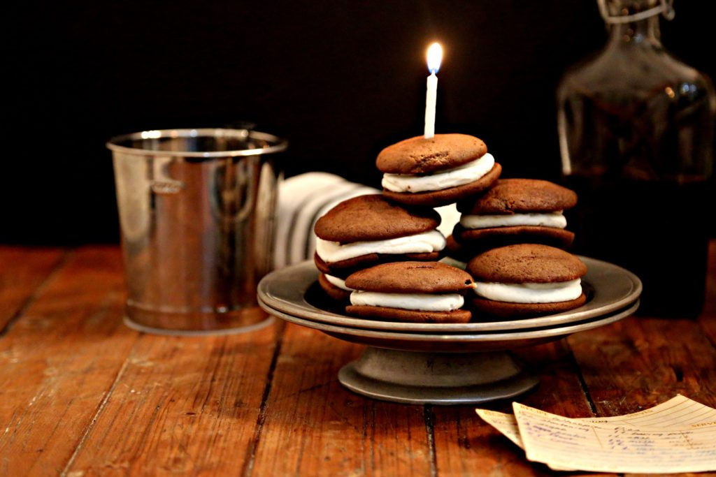 momma's old fashioned whoopies pies on a silver cake plate topped with a birthday candle bottle of vanilla extract and flour sifter
