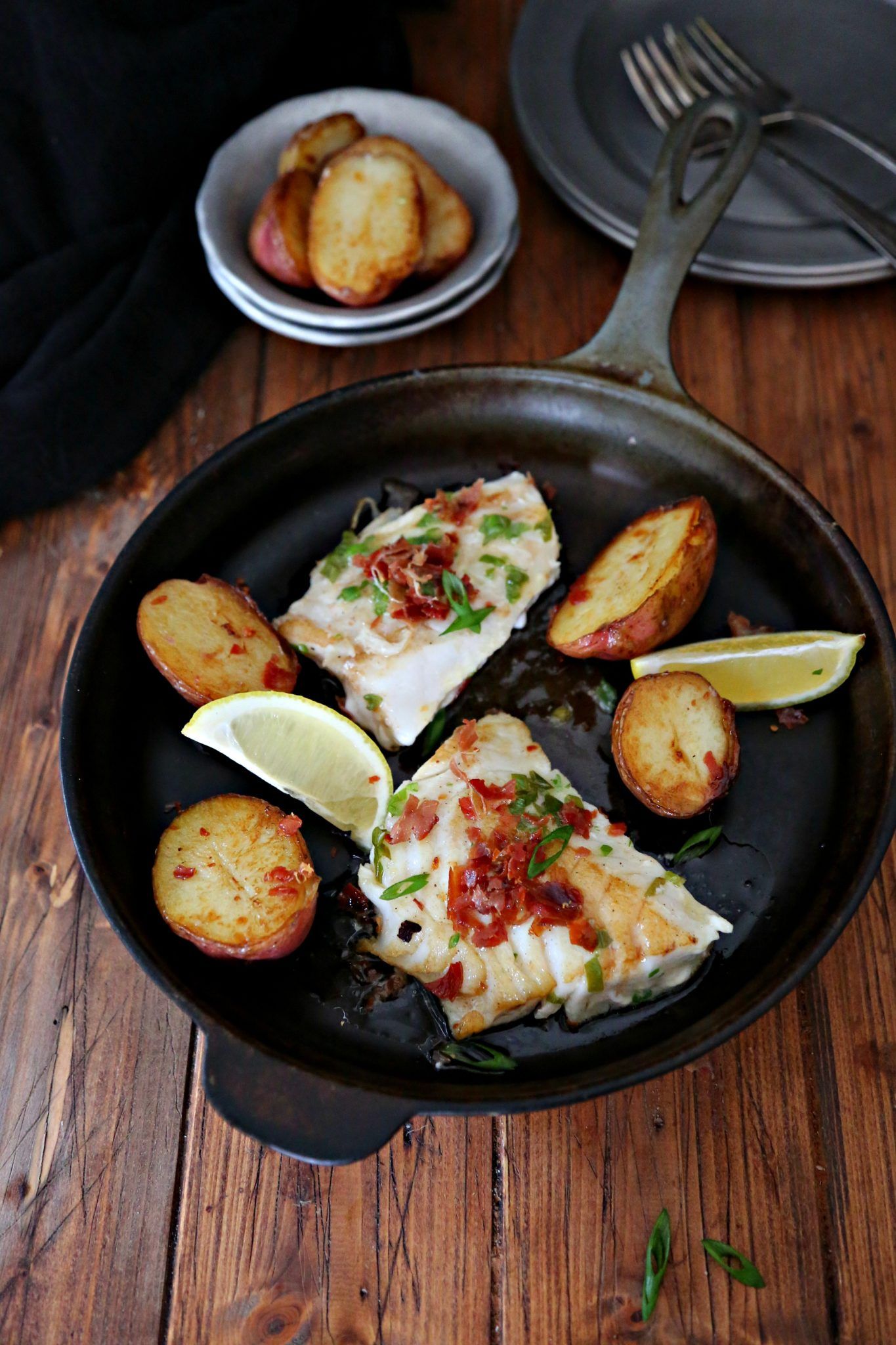 pieces of cod in a black cast iron skillet with potatoes and lemon wedges