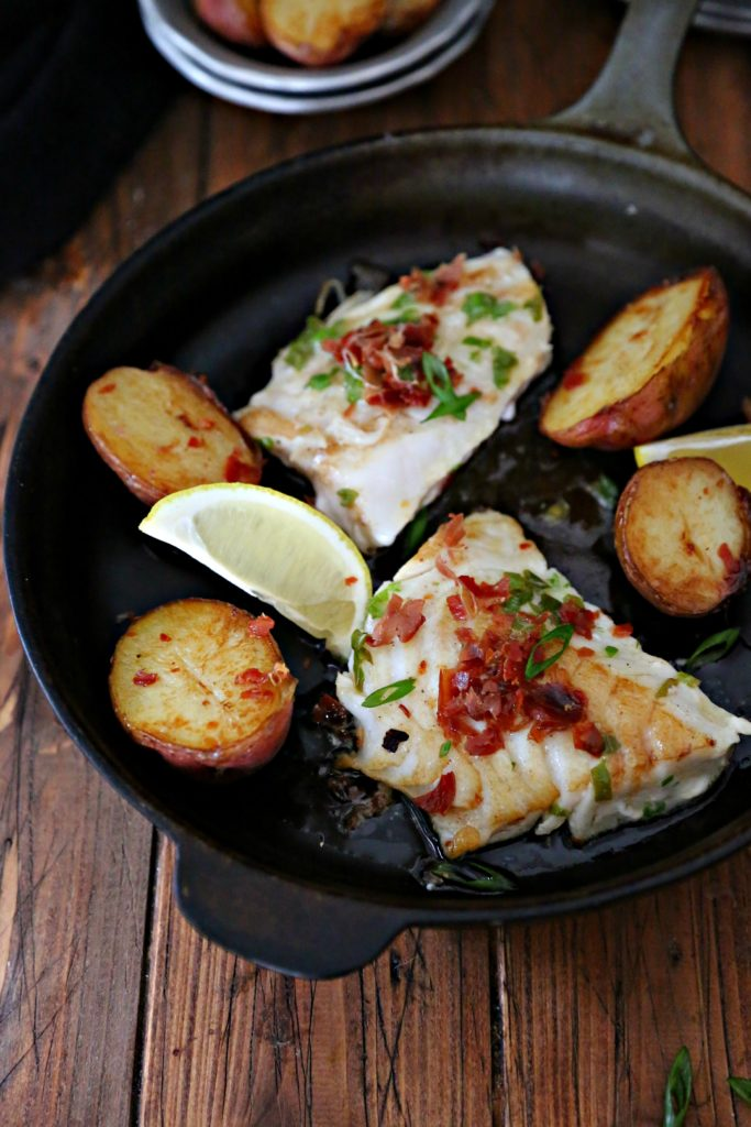 Pieces of cod in black cast iron skillet with potatoes and lemon wedges