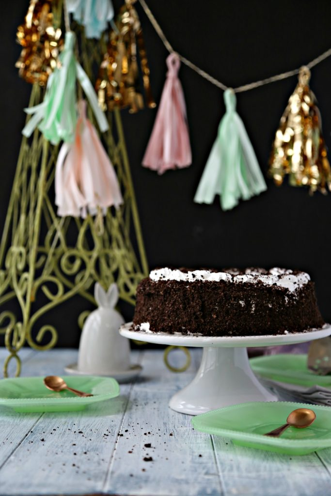 oreo ice cream cake on white cake stand with festive tassels and green plates surrounding