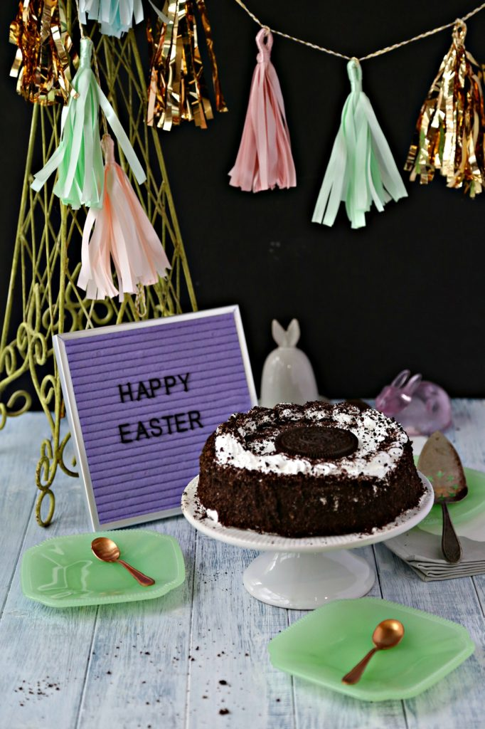 oreo ice cream cake on stand with happy easter sign and tassel decorations