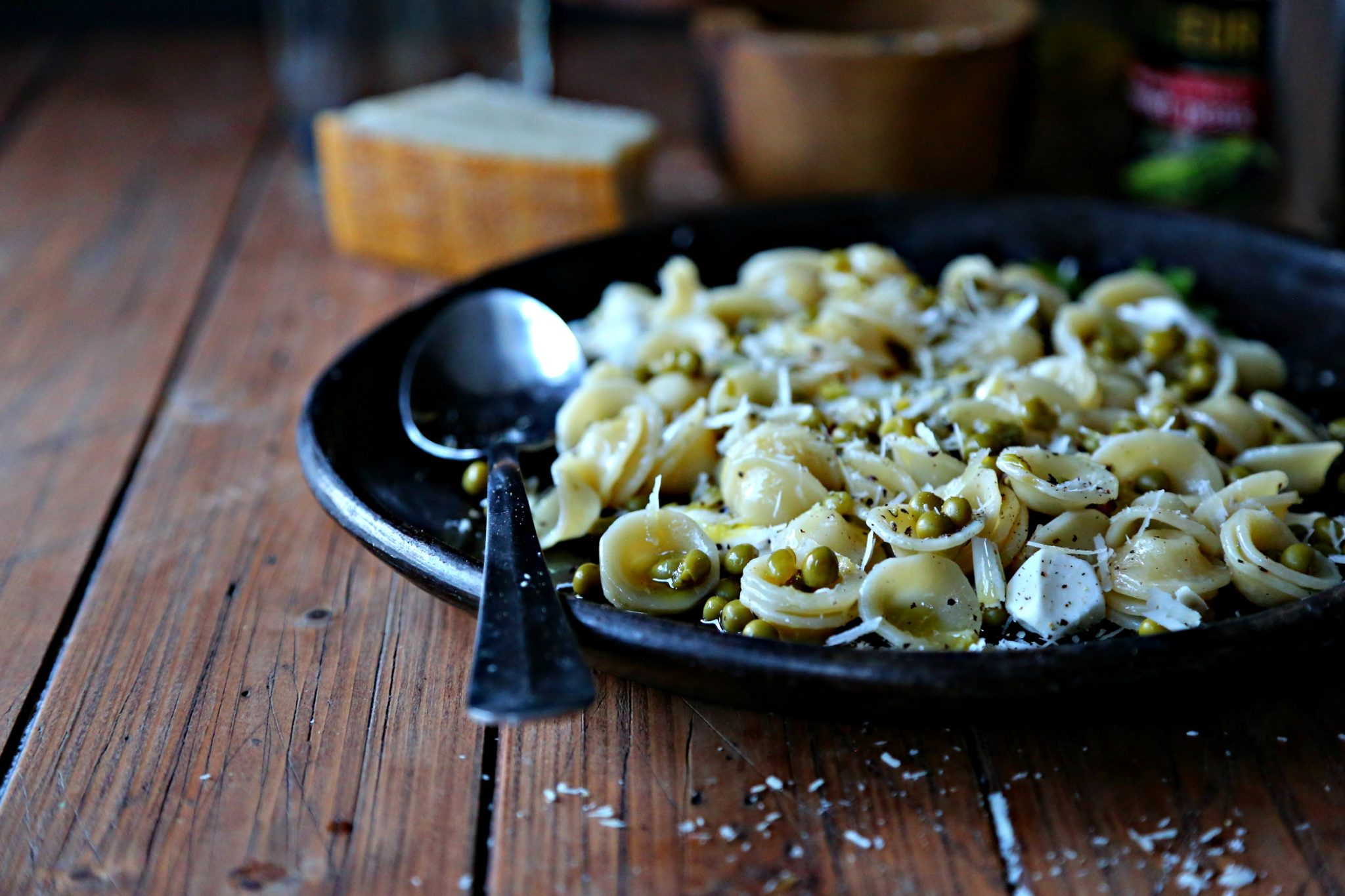 brown plate with silver spoon of orecchiette pasta with peas and parmesan